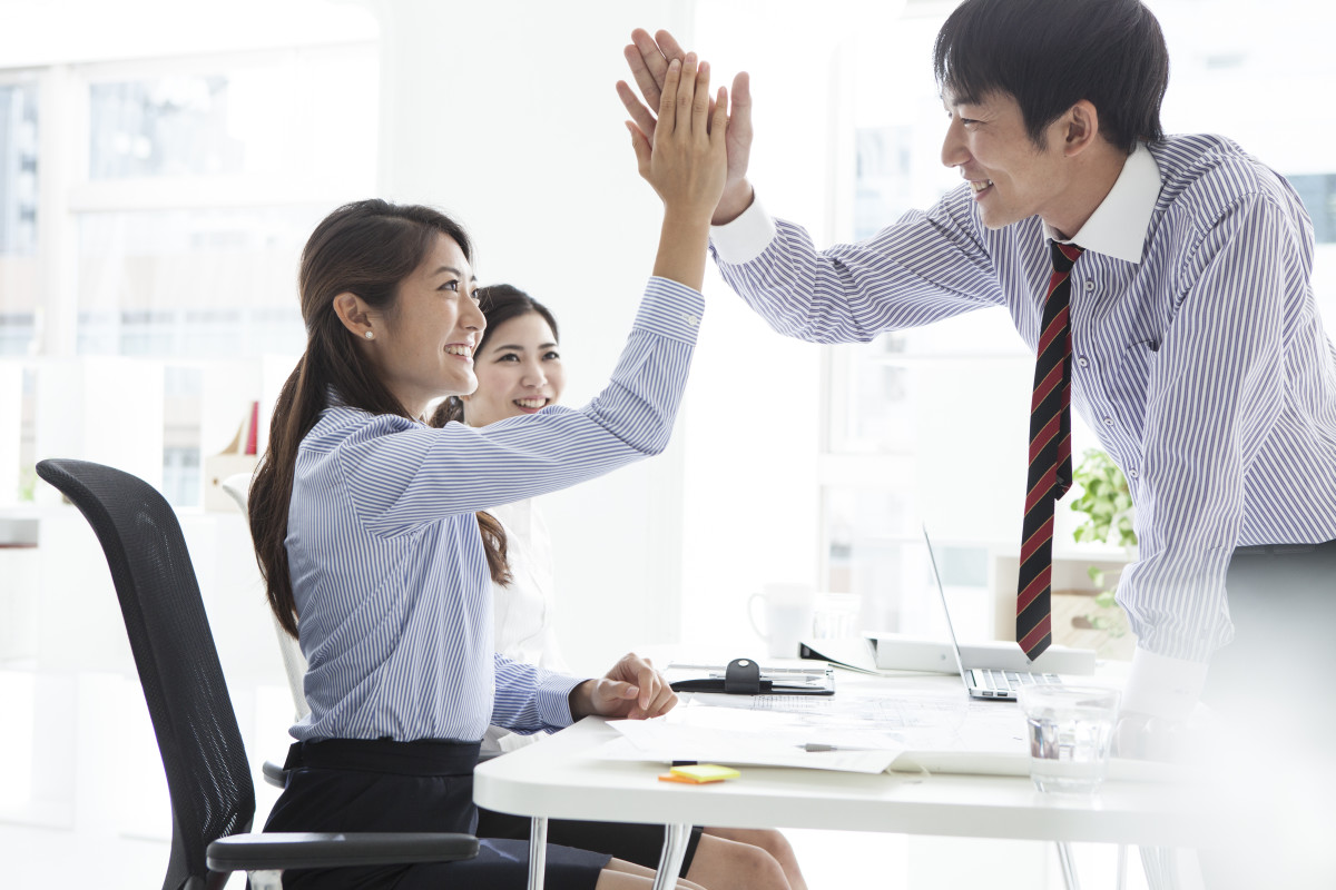 Businessmen and business women have a high five